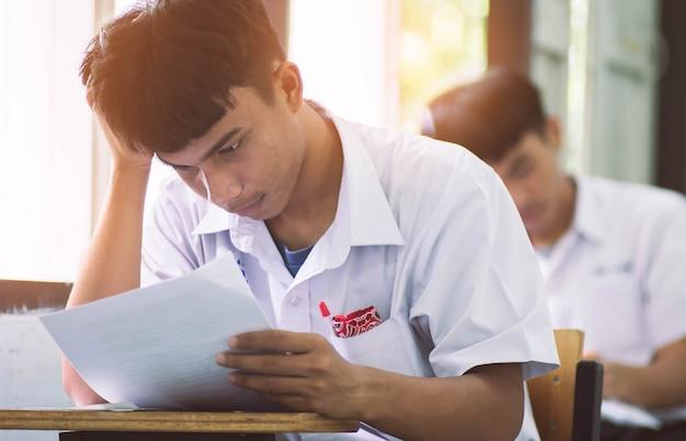 Hombre estudiante leyendo y escribiendo examen con estrés.