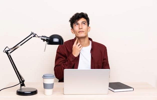 Hombre estudiante en un lugar de trabajo con una computadora portátil
