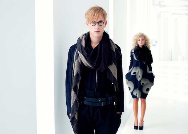 Hombre de estudiante moderno clásico con moda mujer en interior blanco moderno