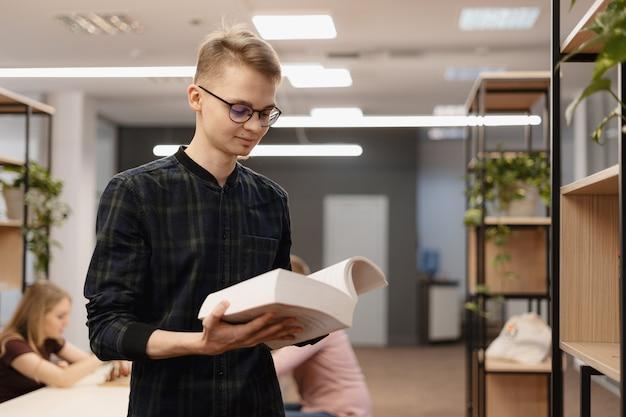 Un hombre estudiante recogiendo libros del estante
