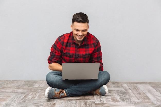 Hombre estudiante trabajando en la computadora portátil mientras está sentado en el piso