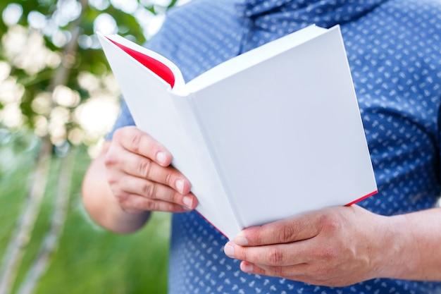 Hombre estudiante vestido con una camisa azul sostiene abierto libro vacío blanco al aire libre