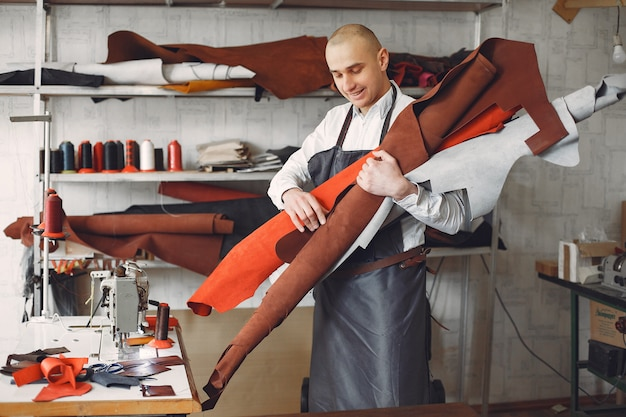 El hombre en un estudio crea artículos de cuero.