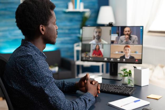 Hombre de etnia africana mediante comunicación por cámara web de conferencia