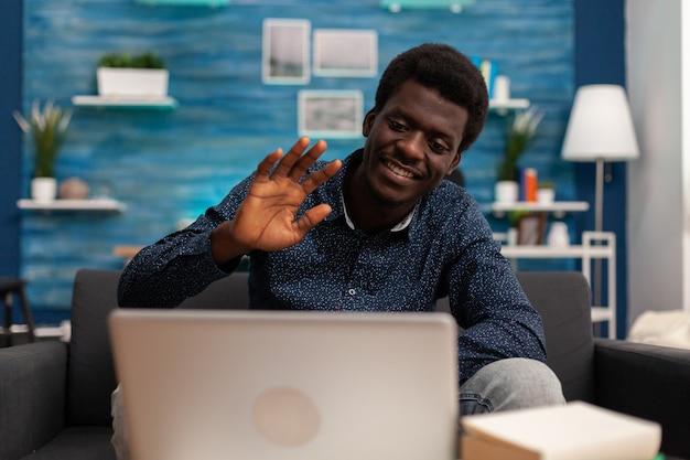 Hombre de etnia afro saludando a amigos remotos durante la conferencia de la reunión de videollamada en línea discutiendo el curso financiero usando la plataforma escolar en la computadora portátil. teletrabajo universitario por videoconferencia