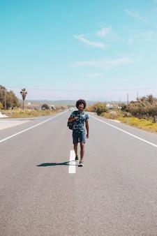 Hombre étnico caminando en la carretera vacía