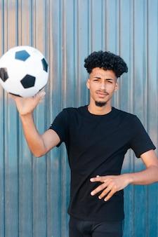 Hombre étnico lanzando fútbol a la cámara