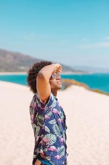 Hombre étnico mirando el cielo en la playa