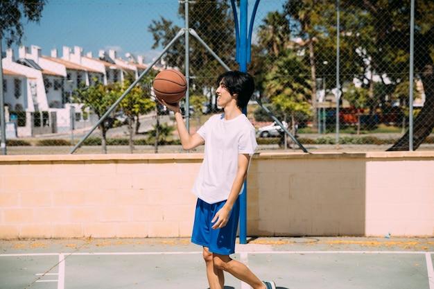 Hombre étnico sosteniendo baloncesto mientras está de pie en el patio