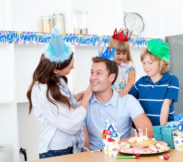 Hombre eufórico celebrando su cumpleaños con su esposa y sus hijos