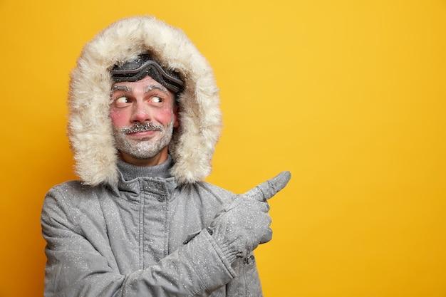 El hombre europeo sin afeitar complacido sugiere participar en la competencia de carreras de esquí viste prendas de vestir exteriores grises en el espacio de la copia