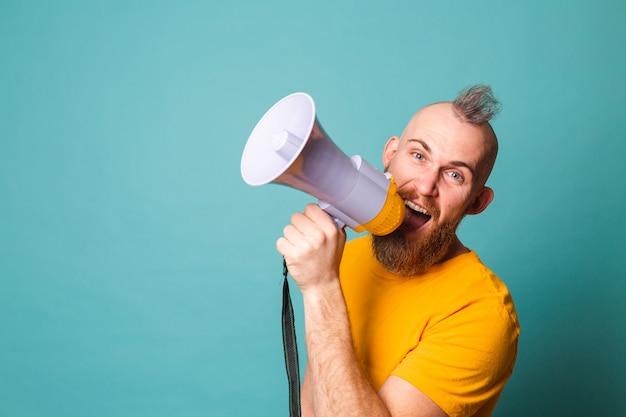 Hombre europeo barbudo con camisa amarilla aislado, gritando loco en el altavoz del megáfono, ¡atención!