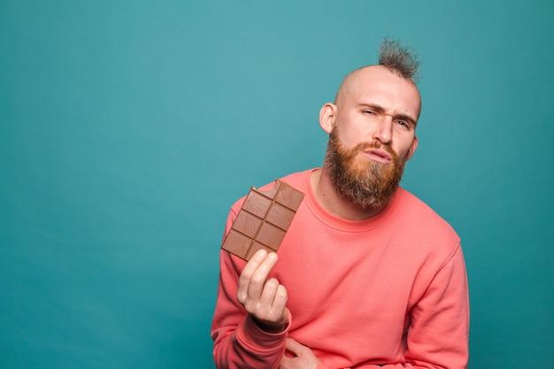 Hombre europeo barbudo en melocotón casual aislado, mantenga chocolate cara infeliz intoxicación alimentaria dolor de estómago
