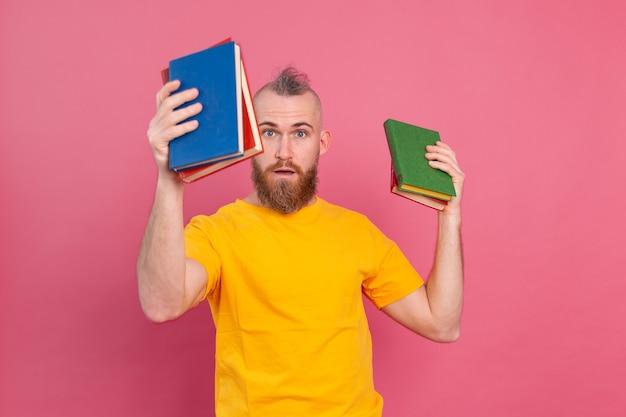 Hombre europeo barbudo con pila de libros en rosa