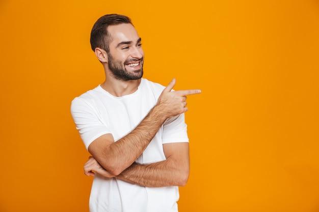 Hombre europeo en camiseta apuntando con el dedo a un lado mientras está de pie, aislado en amarillo