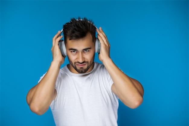 Hombre europeo con camiseta blanca está escuchando música con auriculares