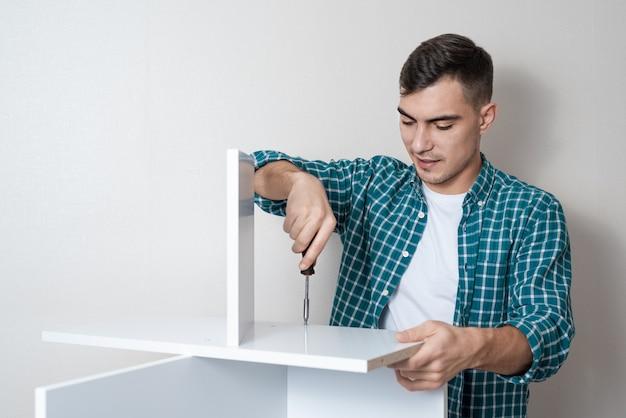 Hombre europeo con un destornillador en la mano recoge una mesa blanca