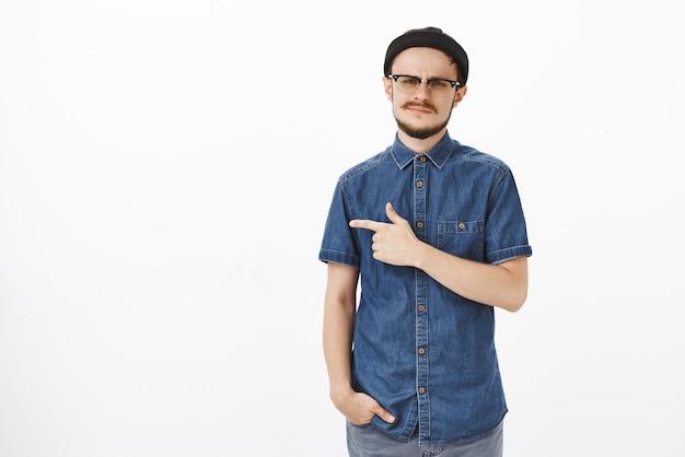 Hombre europeo exigente no impresionado con barba con gafas, gorro de moda y camisa azul, sonriendo y frunciendo el ceño por la disgusto por ser descuidado e insatisfecho, apuntando a la izquierda hacia algo poco impresionante