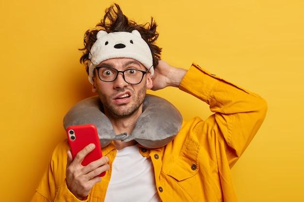 Hombre europeo indignado y desconcertado se rasca la cabeza, lee noticias en línea a través del teléfono móvil, se prepara para viajar, usa una almohada para el cuello, una chaqueta amarilla