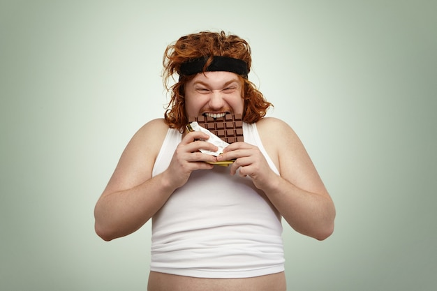 Hombre europeo loco y hambriento con sobrepeso joven pelirroja con buen apetito
