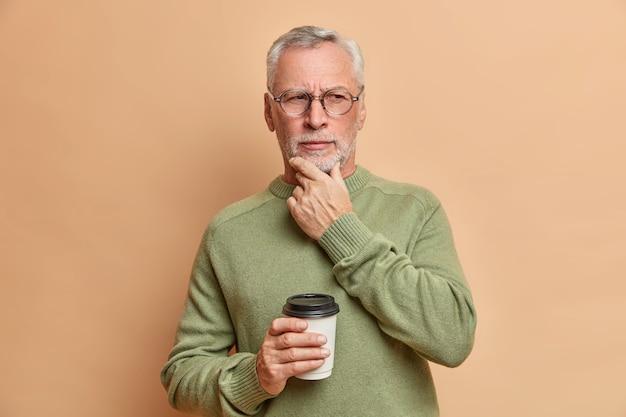 Hombre europeo maduro muy serio sostiene la barbilla mira pensativamente a un lado bebe café para llevar considera algo importante viste un suéter informal y gafas aisladas sobre una pared marrón