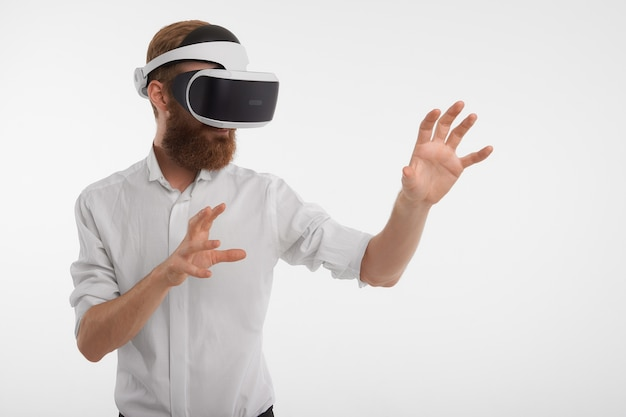 Hombre europeo moderno sin afeitar que usa un casco de realidad virtual 3d que se siente poderoso, extendiendo las manos como si interactuara con algo invisible, jugando videojuegos en su oficina