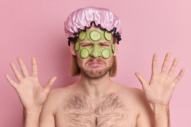 Hombre europeo molesto aplica máscara de pepino verde levanta las manos tiene expresión de insatisfacción reacciona ante algo malo viste sombrero a prueba de agua se encuentra en topless