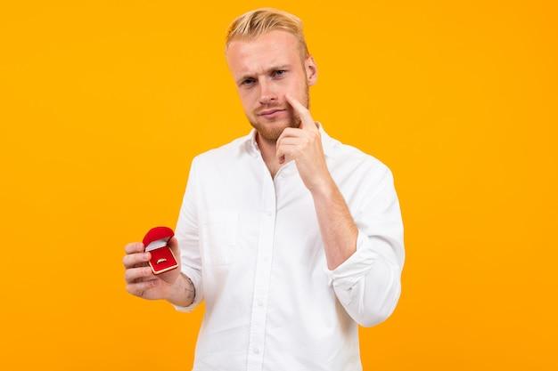 El hombre europeo rubio hace una propuesta que sostiene un anillo en una caja roja en un amarillo.