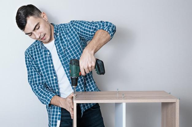 Hombre europeo sonriente confiado recoge muebles con un destornillador eléctrico