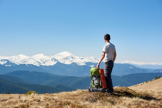 Hombre excursionista disfrutando del sol de la mañana en la cima de la montaña después de una caminata