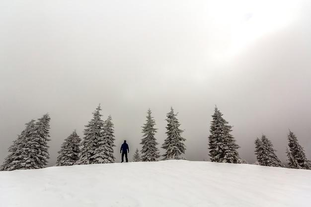 Hombre excursionista de pie en las montañas nevadas de invierno disfrutando de la vista