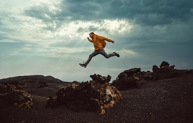 Hombre excursionista saltando por encima de la montaña. libertad, riesgo, éxito y desafío. centrarse en el hombre