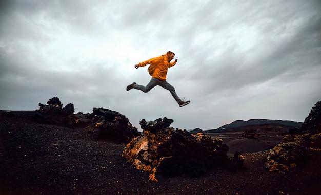 Hombre excursionista saltando por encima de la montaña.