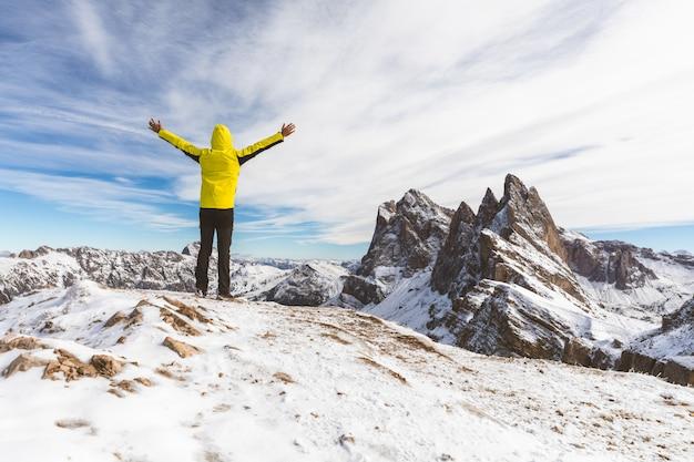 Hombre exitoso en la cima de una montaña nevada