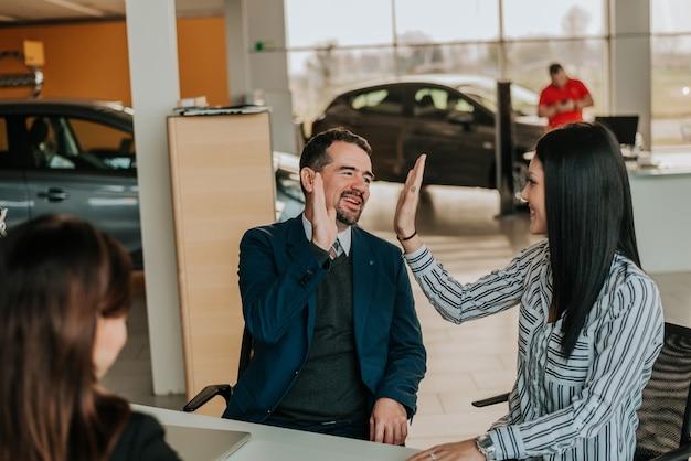 Hombre exitoso comprando hija su primer carro.