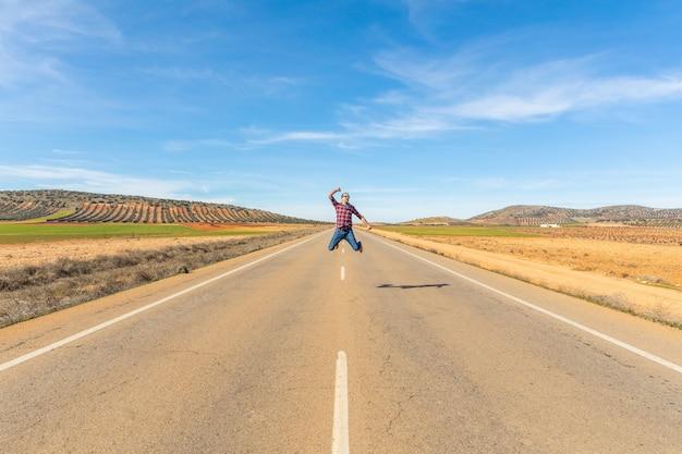Hombre exitoso feliz saltando en camino de campo