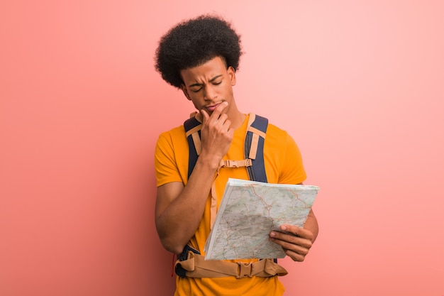 Hombre explorador afroamericano joven que sostiene un mapa que duda y confuso