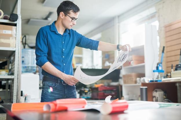Hombre explorando papel impreso en tipografía