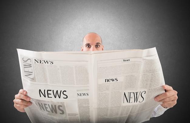 Hombre con expresión de asombro leyendo un periódico