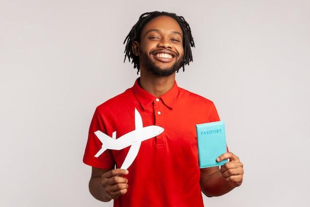 Hombre con expresión feliz sosteniendo pasaporte y avión de papel en manos planeando vacaciones en el extranjero.