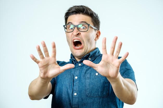 Hombre con expresión de miedo en su rostro haciendo gestos de miedo con las palmas