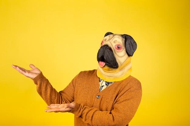 Hombre expresivo con máscara de pug en una pared amarilla con espacio para texto