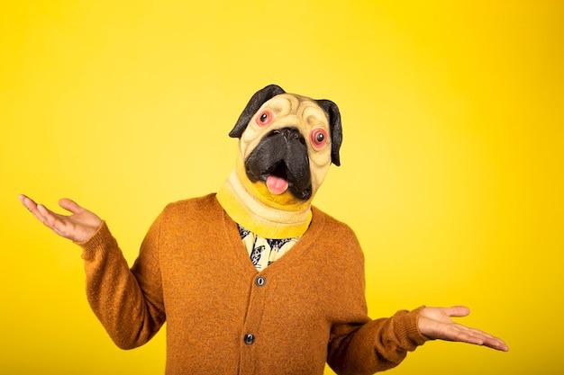 Hombre expresivo con máscara de pug en una pared amarilla