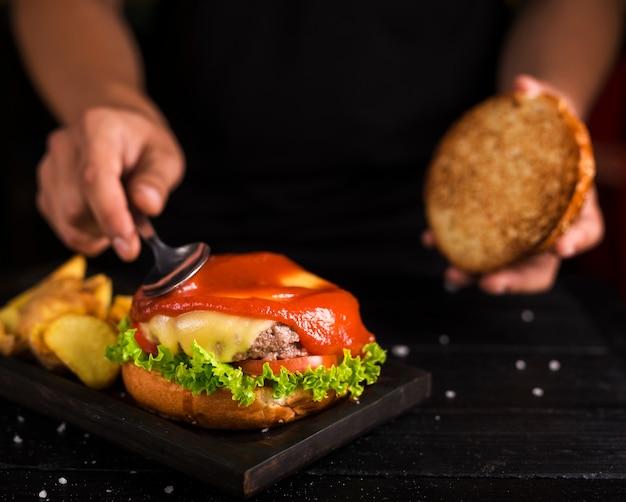 Hombre extendiendo ketchup en sabrosa hamburguesa de ternera