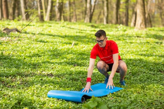 El hombre extiende una estera de yoga azul en un parque sobre hierba verde para ejercicios y relajación. estilo de vida saludable