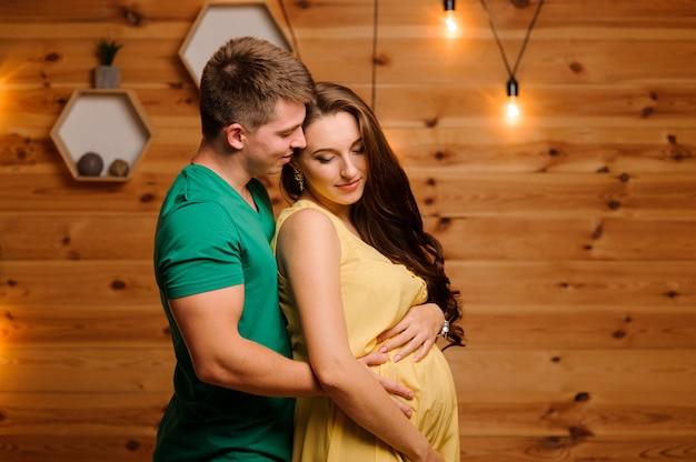 Hombre feliz abrazando a su bella esposa embarazada en el fondo de guirnalda