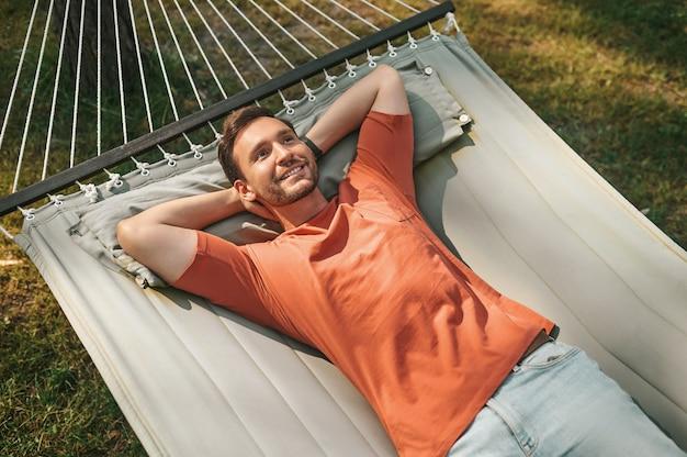 Hombre feliz acostado pensando en una hamaca en la naturaleza