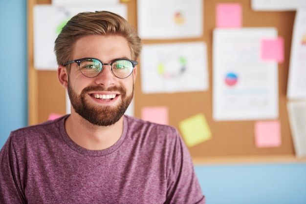 Hombre feliz con anteojos sonriendo en la oficina
