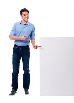 Hombre feliz apuntando en la pizarra blanca