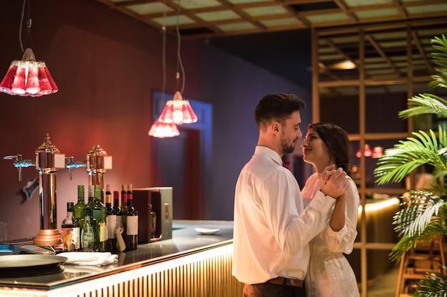 Hombre feliz bailando con mujer alegre cerca de barra de bar